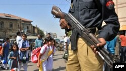 A Pakistani policeman stands guard as students leave school in Karachi