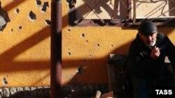 Чоловік сидить біля пошкодженої обстрілами стіни, Дебальцеве, 25 лютого 2015 року