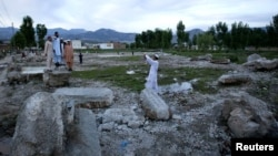 A man takes a picture of his friends on the demolished site of the compound of Osama bin Laden in Abbottabad in May.