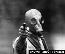 An unidentified man during a training exercise with pistols and gas masks in 1967.