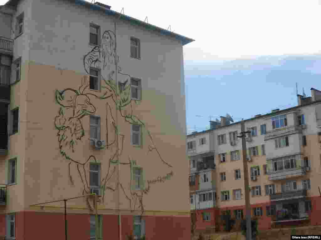 Граффити на фасаде: женщина верхом на верблюде.