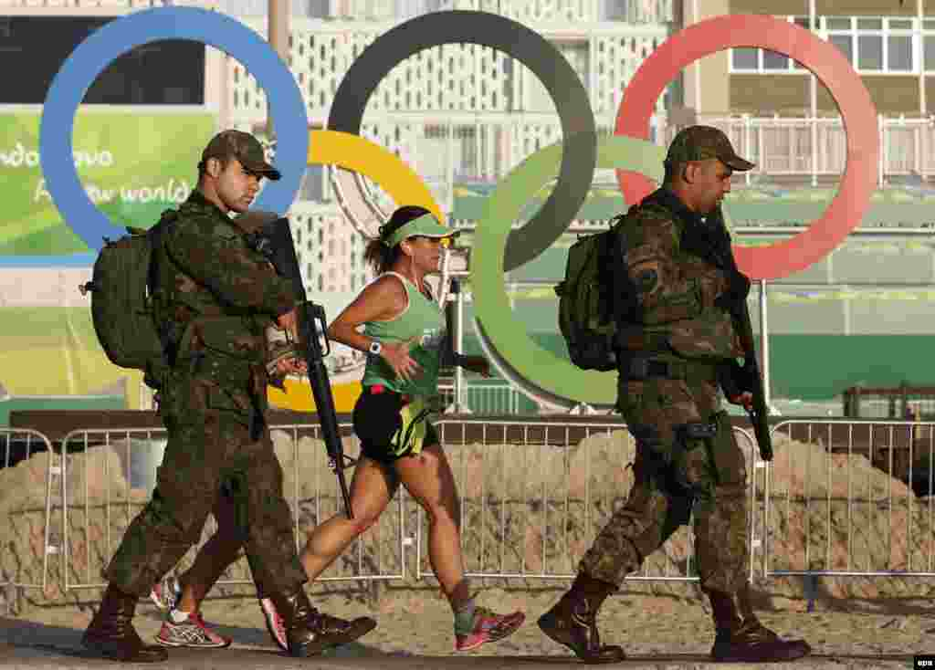 Special military police pass the Olympic rings next to morning joggers during the Rio 2016 Olympic Games, on Copacabana Beach in Rio de Janeiro. (epa/Barbara Walton)