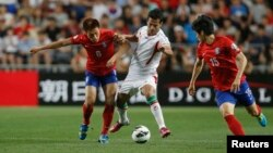 Iran's Masoud Shojaei (center) challenges South Korea's Lee Myoung-ju (left) and Kim Chang-soo during their World Cup qualifying soccer match in Ulsan.