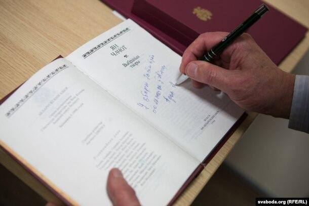Адам Мальдзіс падпісвае кнігу амбасадару Паўліку