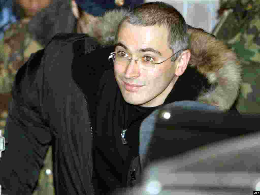 Russian police escort the former Yukos oil chief as he leaves a courthouse in Moscow on December 23, 2003.