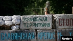 Ukraine -- A pro-Russian militant stands at a barricade at the police headquarters in the eastern town of Slovyansk, June 5, 2014
