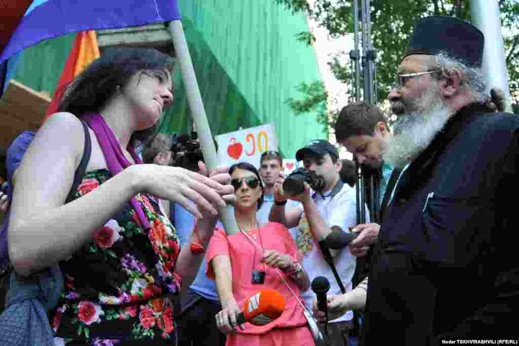 Gay rights activists speak with an Orthodox priest during the International Day Against Homophobia in Tbilisi on May 17.