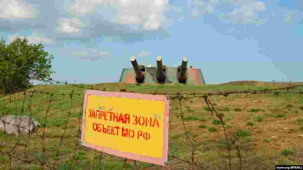 Территория огорожена колючей проволокой. Видны орудия левой башни бронебашенной батареи №30