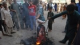 PAKISTAN -- Pakistani protesters burn a poster image of Christian woman Asia Bibi, who has spent eight-years on death row accused of blasphemy and acquitted by a Supreme Court, in Hyderabad, Pakistan, Thursday, Nov. 1, 2018