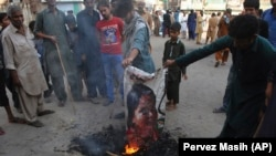Pakistani protesters burn a poster image of Christian woman Asia Bibi in the southern city of Hyderabad on November 1.