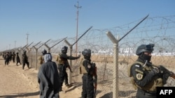Iraqi SWAT forces stand guard outside Camp Ashraf during a protest on December 9 by Iraqis calling for the camp to be closed and for its residents to be deported.