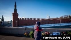 Женщина рядом с местом, где был убит российский оппозиционный политик Борис Немцов на Большом Москворецком мосту. 10 января 2018 года.
