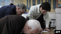 Iranians scrutinize their ballots at a polling station in Tehran on June 12.