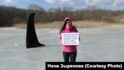 """Нина Зырянова с плакатом против """"китовой тюрьмы"""""""