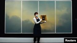 کارمند گالری تابلوی خودنگاری رامبراند را در دست گرفته و پشت سر او نیز اثر معروف گرهارد ریختر قرار دارد.