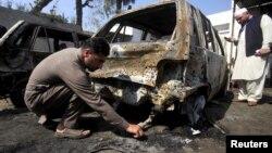 Një polic duke kërkuar prova në vendin e sulmit vetëvrasës në Shabqadar në Pakistan