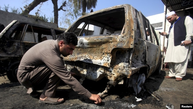 A Pakistani policeman looks for evidence after a deadly suicide attack in Shabqadar on March 7.