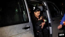 The Dibrani's family get out of a van while under police escort in the northern Kosovar city of Mitrovica, after the family were attacked on October 20.
