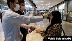 Жительница Тегерана проходит проходит проверку на инфицирование при входе в торговый центр. 3 марта 2020