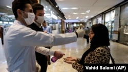 Iran -- A woman has her temperature checked and her hands disinfected as she enters the Palladium Shopping Center in Tehran, March 3, 2020