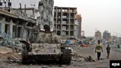Өртенген әскери танк қаңқасы жанынан өтіп бара жатқан адамдар. Аден, Йемен. 19 тамыз 2015 жыл. (Көрнекі сурет)