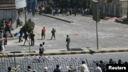 Government backers break a road barrier to reach antigovernment protesters during clashes in Sanaa on February 17.