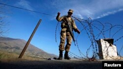A soldier creates a barrier using barbed wire at a security checkpoint in the Swat valley region. (file photo)