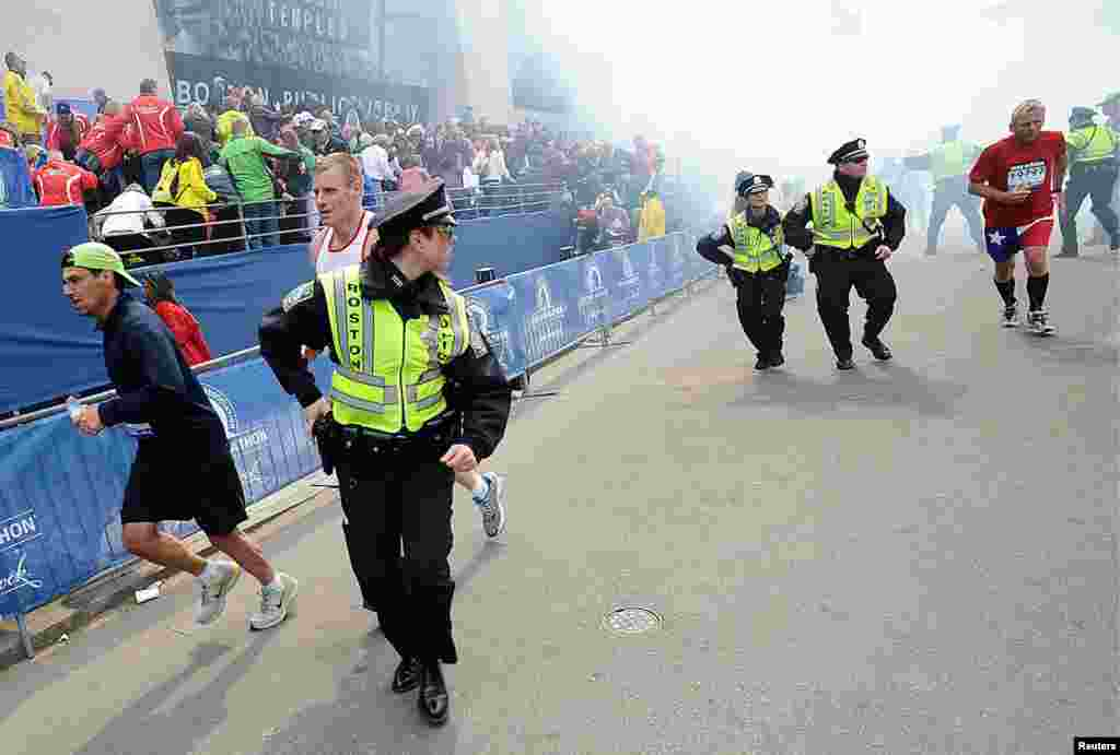 Police and runners react after two explosions at the Boston Marathon.