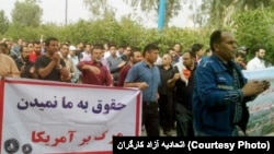 "A protest by Iranian steel workers over unpaid wages on March 17, 2018. The banner mocks the regime by saying, ""They don't pay us - Death to America""."