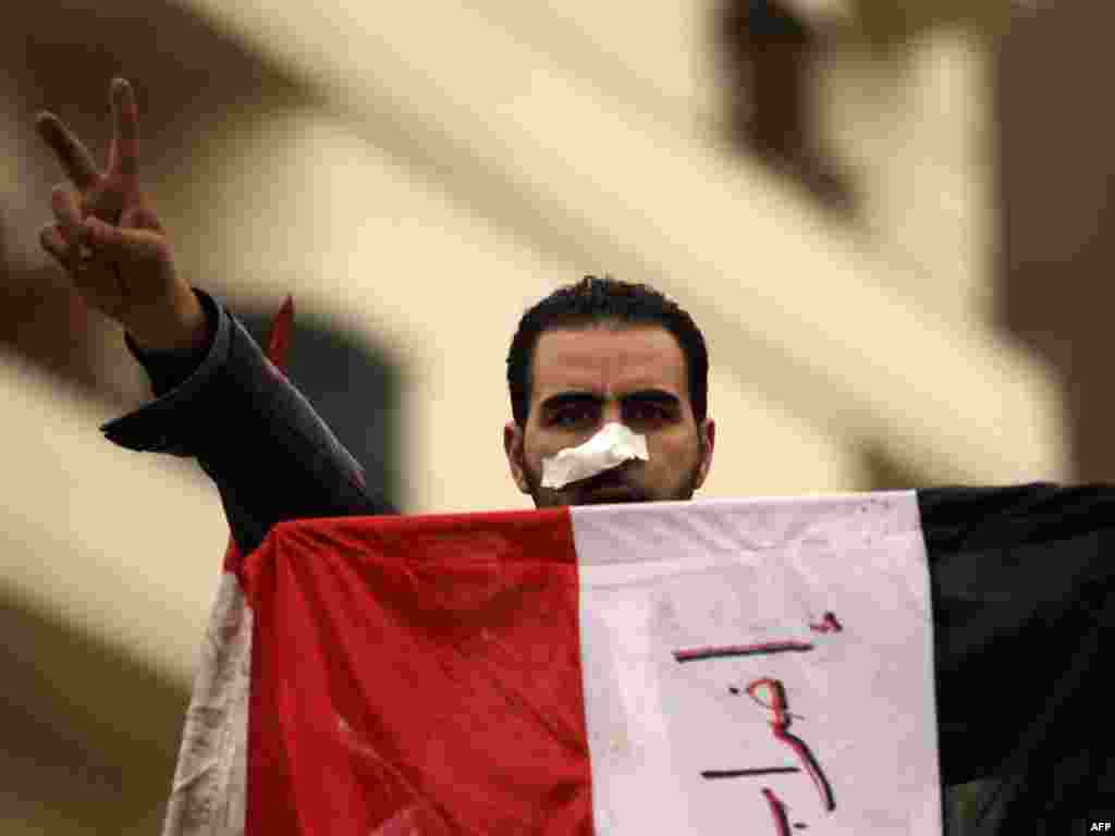 An antigovernment protester flashes the victory sign while holding his national flag in Tahrir Square on February 5.