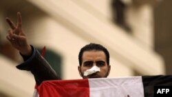 An antigovernment protester flashes the victory sign while holding the national flag in Tahrir Square in Cairo.