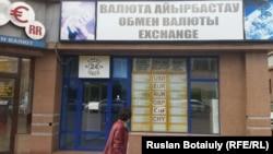 Женщина проходит рядом с обменным пунктом с пустым табло курсов покупки и продажи валют. Астана, 17 сентября 2015 года.