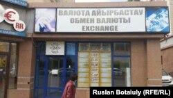 Валюта бағамы жазылмаған табло жанынан өтіп бара жатқан әйел. Астана, 2015 жылдың қыркүйегі.