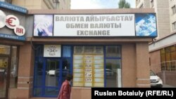 Валюта айырбастау пункті жанынан өтіп бара жатқан әйел. Астана, 17 қыркүйек 2015 жыл.
