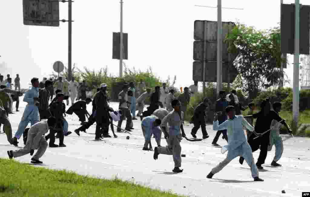 Pakistani demonstrators throw stones at riot police.