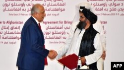 U.S. special envoy Zalmay Khalilzad (left) shakes hands with Taliban co-founder Mullah Abdul Ghani Baradar after signing the peace agreement during a ceremony in the Qatari capital, Doha, on February 29.