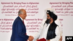 U.S. Special Representative for Afghanistan Reconciliation Zalmay Khalilzad and Taliban co-founder Mullah Abdul Ghani Baradar shake hands after signing a peace agreement during a ceremony in the Qatari capital Doha on February 29.
