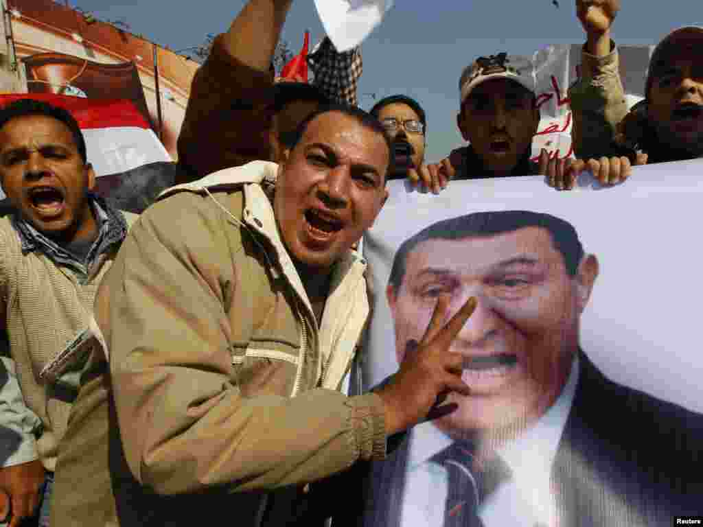 Mubarak supporters carry a banner of the president at a march near Tahrir Square.