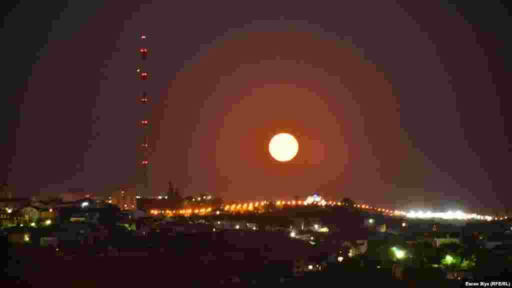 Вид со смотровой площадки на площади Ушакова в Севастополе. Луна висит над горой Воронцова, видна телевизионная вышка и арка, установленная в честь 200-летия города