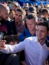 Ukrainian President Volodomyr Zelenskiy takes a selfie with a well-wisher while on a visit to the port city of Mariupol on June 15.