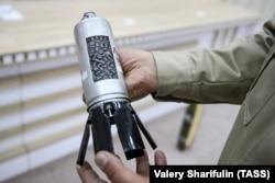 """Азербайджански представител показва касетъчна бомба, изстреляна от """"Смерч"""". Една ракета може да събере в себе си 72 такива мини-бомби."""