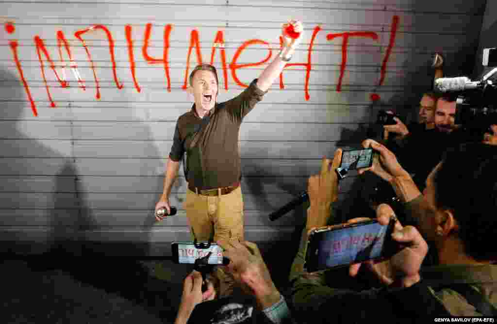 "A protester gestures after writing ""Impeachment"" on a wall during a demonstration outside the Ukrainian presidential residence near Kyiv on September 10. (epa-EFE/Sergey Dolzhenko)"