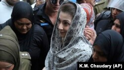 Police officers escort Maryam Nawaz when she appears in an accountability court in Lahore on August 9.