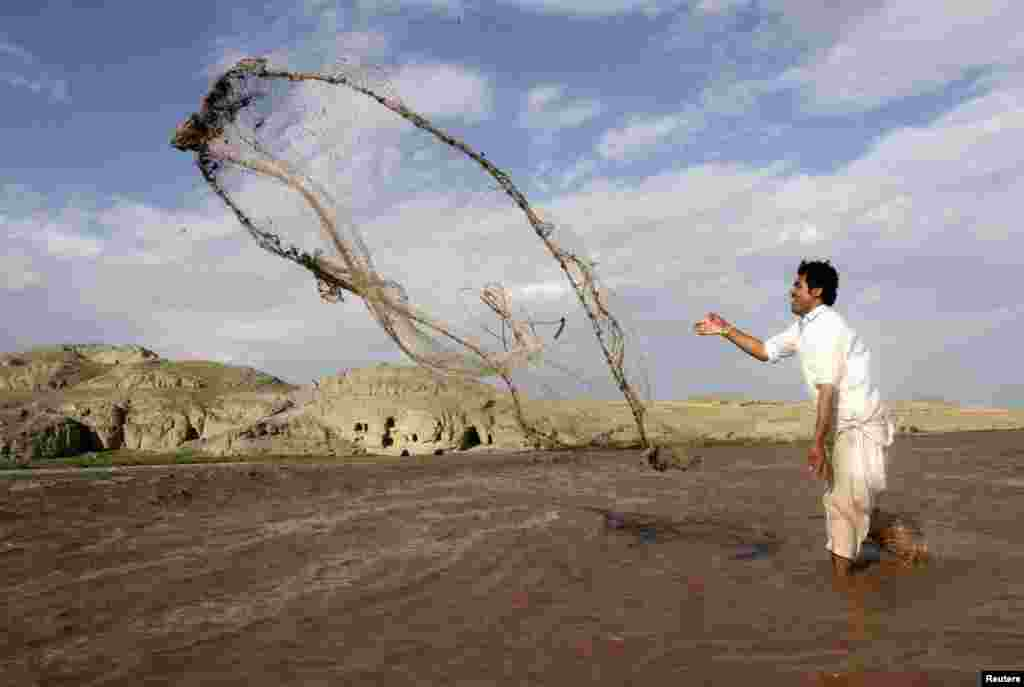 An Afghan man fishes with a net in a river on the outskirts of Jalalabad Province on May 19. (Reuters/Parwiz)
