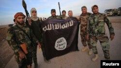 """Шиит сарбаздар """"Ислам мемлекеті"""" содырларымен соғыста қолға түскен туды ұстап тұр. Ирак, 23 қараша 2014 жыл."""