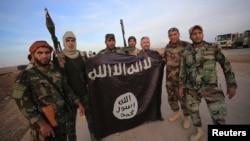 """Иракские бойцы-шииты с флагом группировки """"Исламское государство"""", захваченным у боевиков ИГ. 23 ноября 2014 года."""