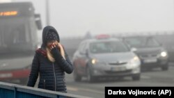 A woman walks through the smog-covered streets of Belgrade.