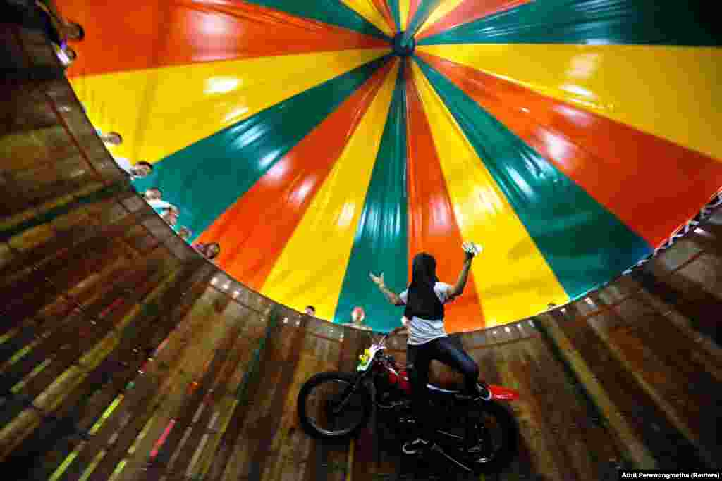 "A stuntman with his face covered rides a motorcycle inside the ""Well of Death"" attraction during a fair in Bangkok, Thailand. (Reuters/Athit Perawongmetha)"