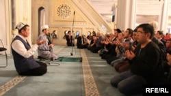 Богослов Абдишукур Нарматов молится вместе с киргизскими мигрантами в Москве, 14 февраля 2016 года