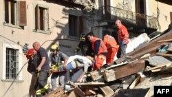 Группа спасателей несет пострадавшего при землетрясении в итальянском городе Аматриче. 24 августа 2016 года.